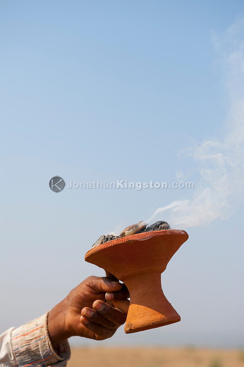 Smoke rises from burning coconut husk during a puja ceremony in India.
