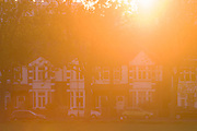 Warm, orange sunlight glare from a setting sun and Edwardian period homes in the south London borough of Lambeth.