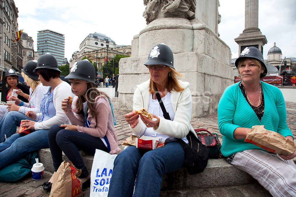 Group of women and girls, visitors to London for the day sit and eat their McDonalds lunch in Trafalgar Square. They are all wearing tourist gift plastic policeman's helmets. This is a very old fashioned souvenir that you still see occasionally.