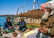 BAS biologist Dr Nigel Bonner (R) enjoyed birthday cake baked by Paulin and Tim Carr aboard Curlew, Grvtviken, South Georgia
