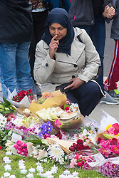 Parliament Square, Westminster, London, June 17th 2016. Following the murder of Jo Cox MP friends and members of the public lay flowers, light candles and leave notes of condolence and love in Parliament Square, opposite the House of Commons. PICTURED: A Muslim woman has a moment of quiet contemplation as she surveys the flowers, notes and candles.