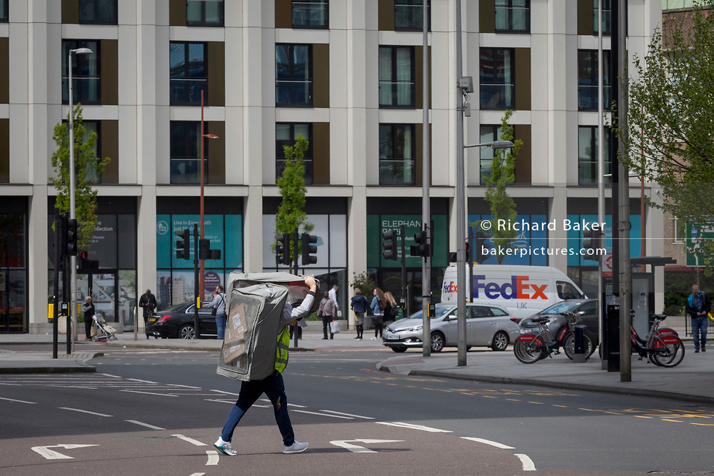 A courier with a load of post and parcels on his back crosses the road at Elephant and Castle with a FedEx van on the other side, on 25th April 2018, in London, England.