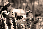 A picture of Hula showing a young girl and an older girl in a Hula pose with one arm outstretched and the other along their face.