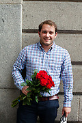 A man waits to go on a date with a bunch of red roses in the Piazza, Covent Garden Market, London, UK