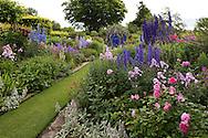 Delphinium 'Nimrod', Delphinium 'Tiddles', Phlox paniculata Othello, Phlox paniculata 'Franz Shubert' and pink rosa in The Sundial Garden at Wollerton Old Hall, Wollerton, Market Drayton, Shropshire, UK