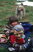 Child wears John Major mask, the Conservative Prime Minister. At Penmaenmawr Quarry area, Stone Circle gathering in Wales. 1990s<br /><br />The British Road Protesters movement began in the early 1990s when the Donga tribe squatted Twyford Down to save this beautiful site, a site of scientific interest SSI from the Ministry of transport's road building programme which threatened to destroy the landscape. The Dongas was the name of the ancient walkways, the paths trodden in the middle ages by people walking down to Winchester. A small tribe were joined by people of all walks of life who came to Twyford Down to defend it. A long hard battle over several years ended in the 'cutting' a new motorway built through this ancient monument and destroying it. <br /><br />The Road Protest movement in Britain continued for many years and more battles were fought in London against the MII both at Wanstead then in Leytonstone, and subsequently at Newbury, and in Sussex. the protesters were very inventive in their use of non violent peaceful direct action. They barricaded themselves into squats, made tree houses, tunnels and have huge demonstrations against the bailliffs, police and security who tried to force their way through the defences of this alternative environmental popular movement. Many of the roads were built eventually and many sites of great beauty lost, but the government had to stand down from its road building policy and eventually the programme was halted. the protests cost the government billions. Out of that movement grew many environmental NGOs who have to this day kept fighting for ecological and sustainable environmental solutions rather than following the cult of the car, petrol and roadbuilding..
