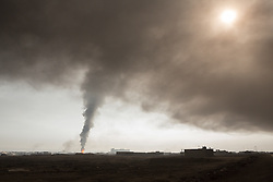 Licensed to London News Pictures. 08/11/2016. Qayyarah, Iraq. Smoke from a burning oil valve rises from within the town of Qayyarah, Iraq. Oil wells in and around the town of Qayyarah, Iraq, we set alight in July 2016 by Islamic State extremists as the Iraqi military began an offensive to liberated the town.<br /> <br /> For two months the residents of the town have lived under an almost constant smoke cloud, the only respite coming when the wind changes. Those in the town, despite having been freed from ISIS occupation, now live with little power, a water supply tainted with oil that only comes on periodically and an oppressive cloud of smoke that coats everything with thick soot. Many complain of respiratory problems, but the long term health implications for the men, women and children living in the town have yet to be seen. Photo credit: Matt Cetti-Roberts/LNP