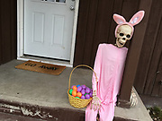 """A skeleton in a pink bunny suit with an easter basket on the front porch of a home in Kalispell, Montana. The doormat reads """"GO AWAY."""""""