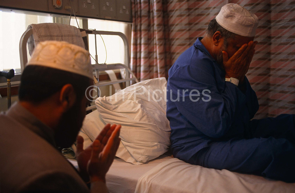 """A Muslim community Imam prays at the bedside of a patient who is staying on the Phyllis Friend surgical ward, Royal London Hospital, Whitechapel, London. They both hold out their hands in prayer and the patient puts them to his face. It is daylight behind the bed but the two men are lit by artificial light from a bulb. The Royal London is one of London's oldest, having been founded in 1740 and is a major teaching hospital in Whitechapel, East London. It is part of the Barts and the London NHS Trust, alongside St Bartholomew's Hospital (""""Barts""""), which is a couple of miles away. Because of the cultural profile of East London, patients tend to be from many faiths, speaking many languages."""