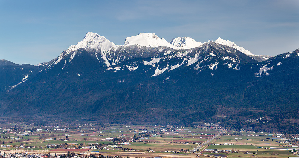 The Peaks of the Mount Cheam Range tower over farmland in Chilliwack. The peaks are (from L to R):  Cheam Peak (Lhílheqey), Lady Peak, Knight Peak, and Welch Peak. Mount Archibald is in front of the Cheam Range between Knight and Welch Peaks. Photographed from Hillkeep Regional Park in Chilliwack, British Columbia, Canada.
