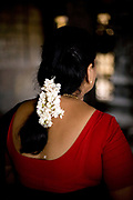 A woman with jasmine flowers in her hair, prays at a shrine in the Murugan Temple in Swamimalai, Tamil Nadu, India