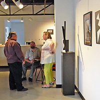 Gallery Organizer, Robert Gallegos, left, talks with visitors at the Route 66 Gallery's Black and White Summer show Saturday  in Grants.