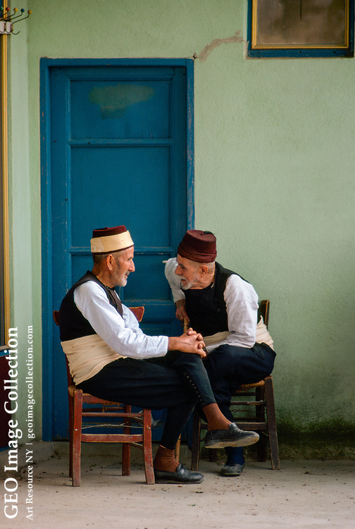 Two Muslim men talking. Gold band on fez indicates he made the haj.