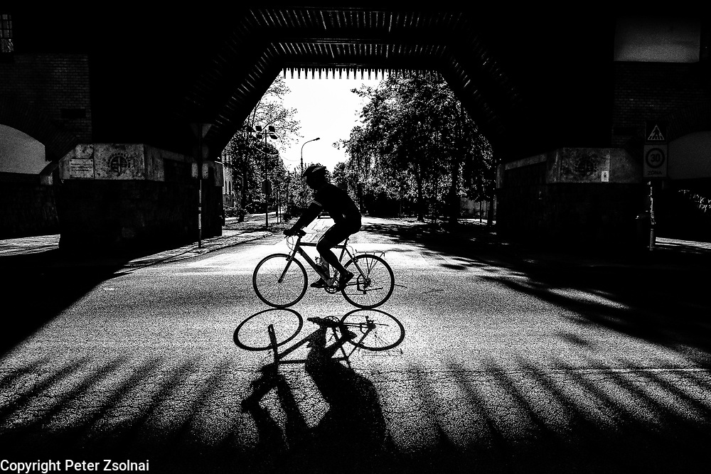 A cyclist riding by infront of a gate in Wekerle that is an beautiful rural neighborhood of Budapest, Hungary