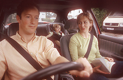 Family sitting in car with father driving; mother map reading and young child strapped into car seat,