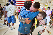 16 JUNE 2010 - PHOENIX, AZ: Sgt 1st Class Robert Lynch from Phoenix (CENTER) hugs his sons, John Lynch, 12, and Brian Lynch, 8, upon his return at the 161st Air Refueling Wing hangar at Sky Harbor Airport in Phoenix Wednesday. Members of the 3666th Maintenance Company of the Arizona Army National Guard returned to Phoenix Wednesday after serving in Iraq (CQ).   PHOTO BY JACK KURTZ