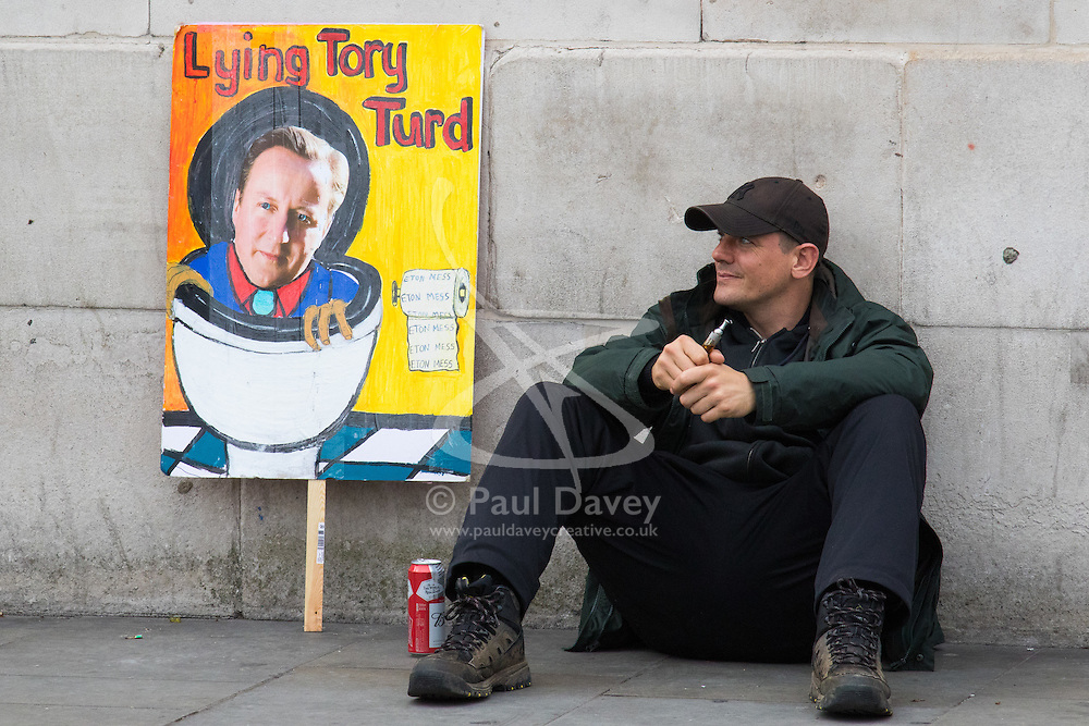 """London, April 16th 2016. A man sits in front of the national gallery next to a discarded placard after thousands of people supported by trade unions and other rights organisations demonstrate against the policies of the Tory government, including austerity and perceived favouring of """"the rich"""" over """"the poor""""."""