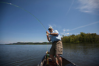 Angler and guide Drew Price plays a fly caught northern pike, lake champlain