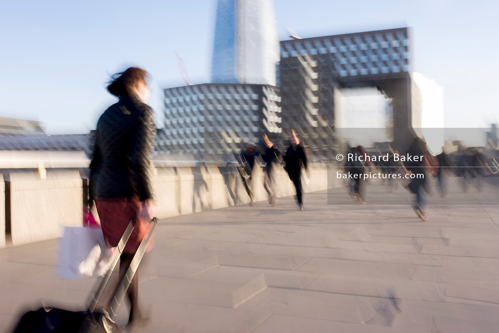 Blurred commuters walk over London Bridge, south from the City of London towards Southwark.