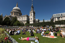 © Licensed to London News Pictures. 12/08/2016. LONDON, UK.  Office workers on their lunchbreak opposite St Paul's Cathedral during the hot and sunny weather this lunchtime in London this lunchtime.  Photo credit: Vickie Flores/LNP