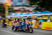 "17 OCTOBER 2012 - BANGKOK, THAILAND:      A ""tuk-tuk,"" or three wheeled taxi, on Yaowarat Road during the Vegetarian Festival in Bangkok's Chinatown. The Vegetarian Festival is celebrated throughout Thailand. It is the Thai version of the The Nine Emperor Gods Festival, a nine-day Taoist celebration celebrated in the 9th lunar month of the Chinese calendar. For nine days, those who are participating in the festival dress all in white and abstain from eating meat, poultry, seafood, and dairy products. Vendors and proprietors of restaurants indicate that vegetarian food is for sale at their establishments by putting a yellow flag out with Thai characters for meatless written on it in red.       PHOTO BY JACK KURTZ"
