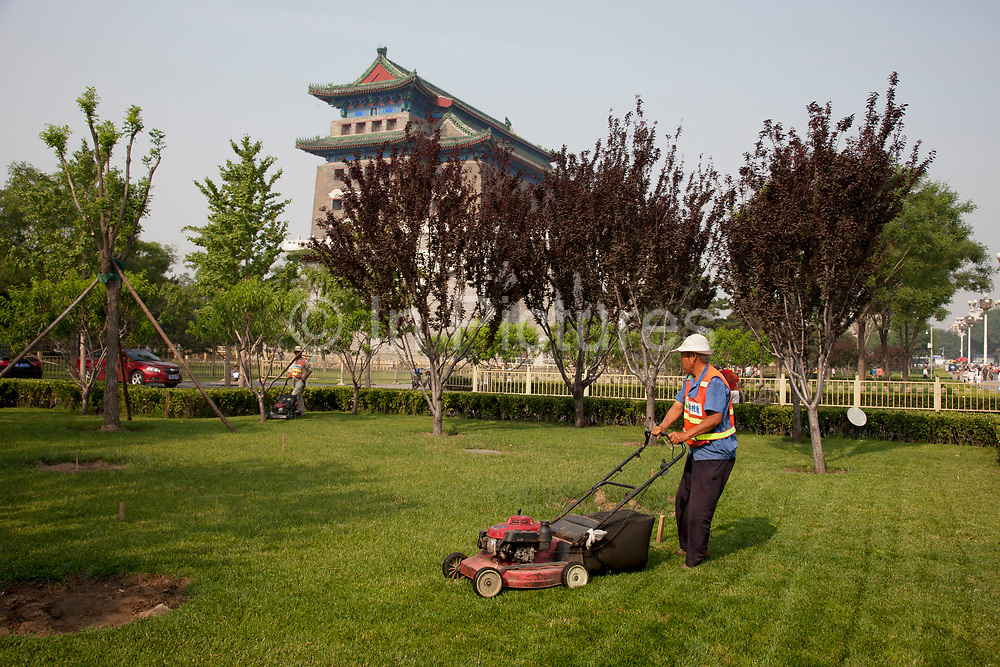 """Man mowing the grass at Qianmen (literally """"Front Gate"""") is a gate in Beijing's historic city wall. The gate is situated to the south of Tiananmen Square and once guarded the southern entry into the Inner City. Although much of Beijing's city walls were demolished, Qianmen remains an important geographical marker of the city. The city's central north-south axis passes through Zhengyangmen's main gate. It was formerly named Lizhengmen meaning """"beautiful portal"""". Zhengyangmen was first built in 1419 during the Ming Dynasty and once consisted of the gatehouse proper and an archery tower."""