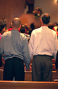Father and son ages 50 and 19 holding hands during church service.  St Paul  Minnesota USA