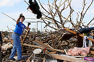 A volunteer throws a piece of recovered clothing at a tornado-destroyed home across the street from the Plaza Towers elementary school in Moore, Oklahoma May 22, 2013. A massive tornado tore through a suburb of Oklahoma City, wiping out whole blocks and killing at least 24.   REUTERS/Rick Wilking (UNITED STATES)