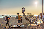 Children play on a sculpture on Brighton seafront at sunset