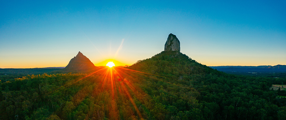 Panoramic aerial view of the setting sun behind Mt Beerwah (left) & Mt Coonowrin, Glass House Mountains, Sunshine Coast Hinterland, Queensland, Australia