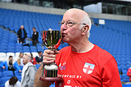 Tommy Charlton of England over 60's kisses the the Just International Cup winners trophy at full time during the world's first Walking Football International match between England and Italy at the American Express Community Stadium, Brighton and Hove, England on 13 May 2018. Picture by Graham Hunt.