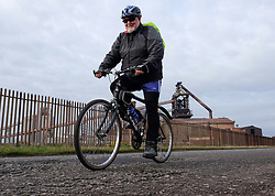 © Licensed to London News Pictures.20/10/15<br /> Redcar, UK. <br /> <br /> A man rides his bike along a road in front of the recently closed SSI UK steel blast furnace in Redcar, England. The closure of the site marks the end of 170 years of steel making heritage on Teesside and was the first of a number of recent closures of steel making plants across the UK.<br /> <br /> Photo credit : Ian Forsyth/LNP