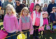 North Merrick, New York, USA. March 31, 2018. Young children, many of the girls dressed in pink, wait behind yellow tape for start of Easter Egg Hunt at the Annual Eggstravaganza, held at Fraser Park and hosted by North and Central Merrick Civic Association (NCMCA) and Merrick's American Legion Auxiliary Unit 1282.
