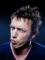 studio portrait on black background of a funny expressive caucasian man puckering annoyed