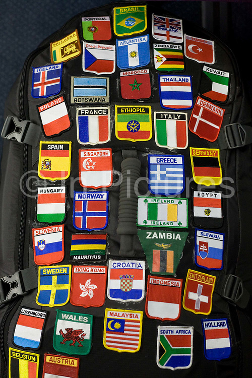 """An accumulation of badges show where a passenger on board a Heathrow Express train to Heathrow Airport has travelled to. Sewn onto the traveller's rucksack, the countries represented by these patches show a much-travelled young person who has amassed a collection of world air miles and travel experiences, with their national flags and emblems on display in a way that adventurers show their routes and wanderlust to others, perhaps as proof of a lifetime wandering the world's borders and airports. As each badge is added, it accounts for new travel companions and the hazards and joys of modern air travel. From writer Alain de Botton's book project """"A Week at the Airport: A Heathrow Diary"""" (2009)."""