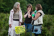Three women in a field of baby tree Christmas trees. Anti-fracking activists join hands to surround the Cuadrilla fracking site. Thousands turned out for a march of solidarity against fracking in Balcombe. The village Balcombe in Sussex is the  centre of fracking by the company Cuadrilla. The march saw anti-fracking movements from the Lancashire and the North, Wales and other communities around the UK under threat of gas and oil exploration by fracking.