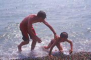 A5EWY9 Two brothers pushing each other as they get out of the sea
