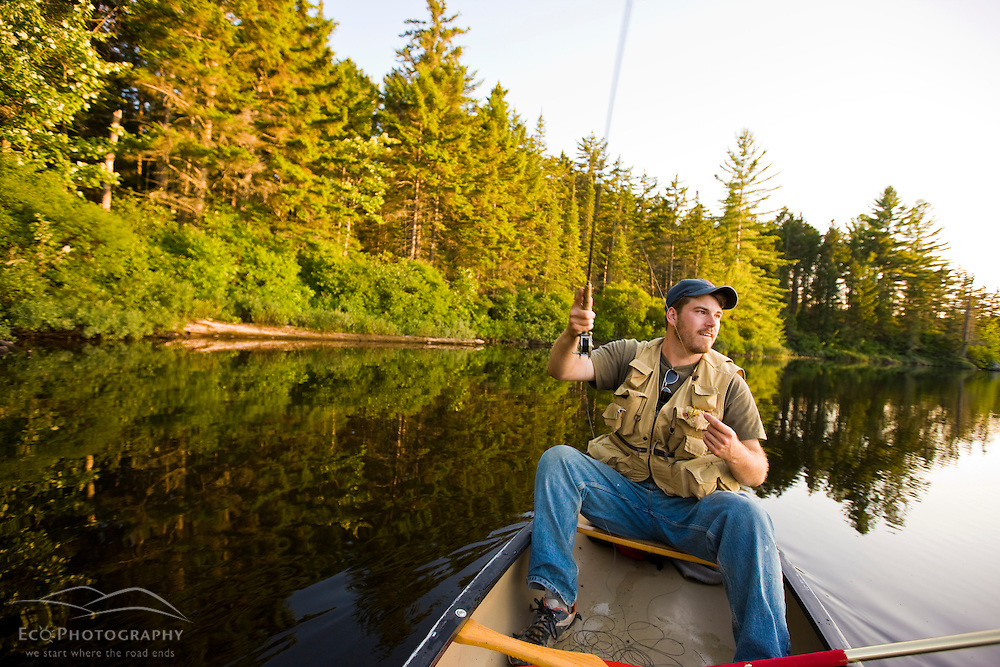 A man fly-fishing from a canoe on Little Greenough Pond in Errol, New Hampshire.