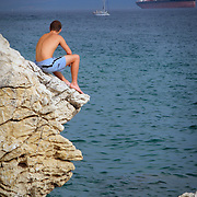 Young man sitting on rock precipice above water, Split, Croatia (August 2007)