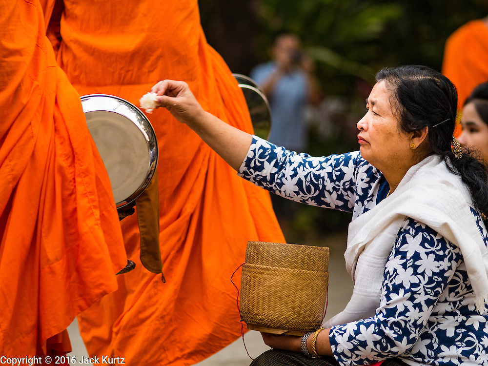 """11 MARCH 2016 - LUANG PRABANG, LAOS:  A Lao woman gives alms to Buddhist monks during the morning tak bat in Luang Prabang. Luang Prabang was named a UNESCO World Heritage Site in 1995. The move saved the city's colonial architecture but the explosion of mass tourism has taken a toll on the city's soul. According to one recent study, a small plot of land that sold for $8,000 three years ago now goes for $120,000. Many longtime residents are selling their homes and moving to small developments around the city. The old homes are then converted to guesthouses, restaurants and spas. The city is famous for the morning """"tak bat,"""" or monks' morning alms rounds. Every morning hundreds of Buddhist monks come out before dawn and walk in a silent procession through the city accepting alms from residents. Now, most of the people presenting alms to the monks are tourists, since so many Lao people have moved outside of the city center. About 50,000 people are thought to live in the Luang Prabang area, the city received more than 530,000 tourists in 2014.      PHOTO BY JACK KURTZ"""