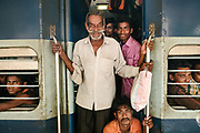 Moustache man. Passengers congregate in one of the many entrances on the Vivek Express, where the doors are always open and people can jump on and off.<br /> Outside the Dibrugarh-Kanyakumari Vivek Express, the longest train route in the Indian Subcontinent. It joins Kanyakumari, Tamil Nadu, which is the southernmost tip of mainland India to Dibrugarh in Assam province, near the border with Burma.