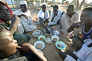 Sudanese refugees enjoy a meal  to mark the end of the month of Ramadan, the Muslim fasting period in the Breidjing Refugee Camp in Eastern Chad. Some of the families in the refugee camp celebrate the festival of Eid al-Fitr by banding together to buy a goat, which they then slaughter and share. Men eat apart from women.
