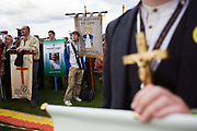Local Catholic church groups with banners await the start of the Hyde Park rally during Pope Benedict XVI's papal tour of Britain 2010, the first visit by a pontiff since 1982. In the foreground, a man holds a crucifix in his hand while behind, pilgrims hold their banners that will be paraded on stage in front of 80,000 prople. Taxpayers footed the £10m bill for non-religious elements, which largely angered a nation still reeling from the financial crisis. Pope Benedict XVI is the head of the biggest Christian denomination in the world, some one billion Roman Catholics, or one in six people. In Britain there are about five million Catholics but only a quarter of Catholics regularly attend Sunday Mass and some churches have closed owing to spending cuts.