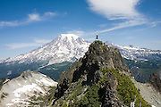 Climber Ian Derrington enjoys the views of Mount Rainier from Unicorn Peak on a traverse of the Tatoosh Range in Mount Rainier National Park, Washington.