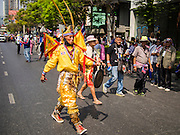 21 JANUARY 2014 - BANGKOK, THAILAND:  A Thai ultra-nationalist supporter of Suthep Thaugsuban marches down Thanon Naradhiwas Rajanagarindra during a march by Suthep Thaugsuban. Suthep, the leader of the anti-government protests and the People's Democratic Reform Committee (PDRC), the umbrella organization of the protests, led a march through the financial district of Bangkok Tuesday. Shutdown Bangkok has entered its second week with no resolution in sight. Suthep is still demanding the caretaker government of Prime Minister Yingluck Shinawatra resign and the PM says she won't resign and intends to go ahead with the election.    PHOTO BY JACK KURTZ