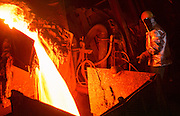 29 JANUARY 1999  - EL PASO, TEXAS: A worker at the Asarco copper smelter in El Paso, Texas, monitors molten copper coming out of the furnace. Asarco mothballed the smelter for at least three years because of low prices in the copper industry. In mid 1997, copper was selling for approximately $1.20 per pound, it is currently selling for about .65 cents per pound, forcing copper producers like Asarco to take drastic belt tightening measures. About 370 workers were laid off as the plant's machinery was mothballed. Closure of the Asarco smelter comes on the heels of the closure of copper mines in southern New Mexico owned by the Phelps-Dodge company, an Asarco competitor. Asarco officials have said they may reopen the plant if copper prices rebound. Photo by Jack Kurtz / ZUMA Press
