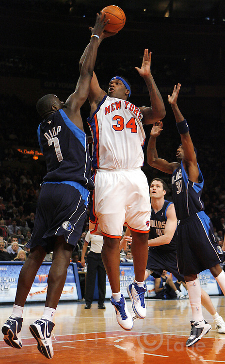 The Knicks' Eddy Curry (C) shoots over the Mavericks' DaSagana Diop (L) and Jason Terry (R) during the first half of the game between the Dallas Mavericks and the New York Knicks at Madison Square Garden in New York, New York on Tuesday 20 March 2007.