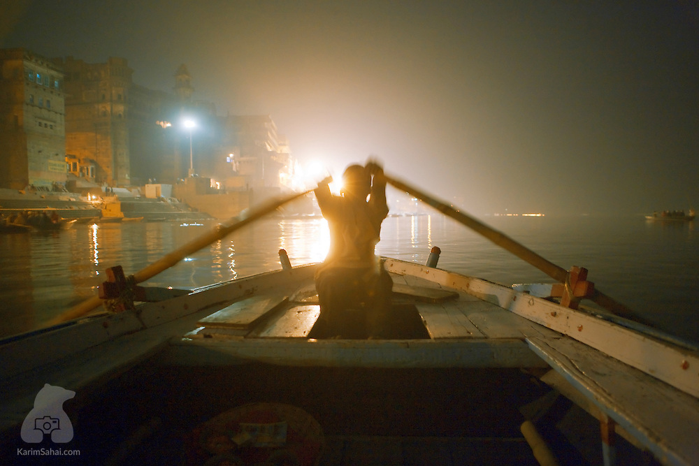 """Man rowing on the sacred Ganges river in Varanasi, Uttar Pradeh, India.<br /> <br /> The Ganges river lies at the very heart of Hindu faith. It is considered sacred because of its ability to """"wash sins"""" and help attain salvation. Daily cremation rituals take place on the river shores and the ashes of the departed are cast into the water, with the belief that the soul travels to heaven."""