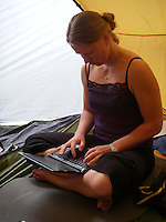 Girl writing on laptop in tent