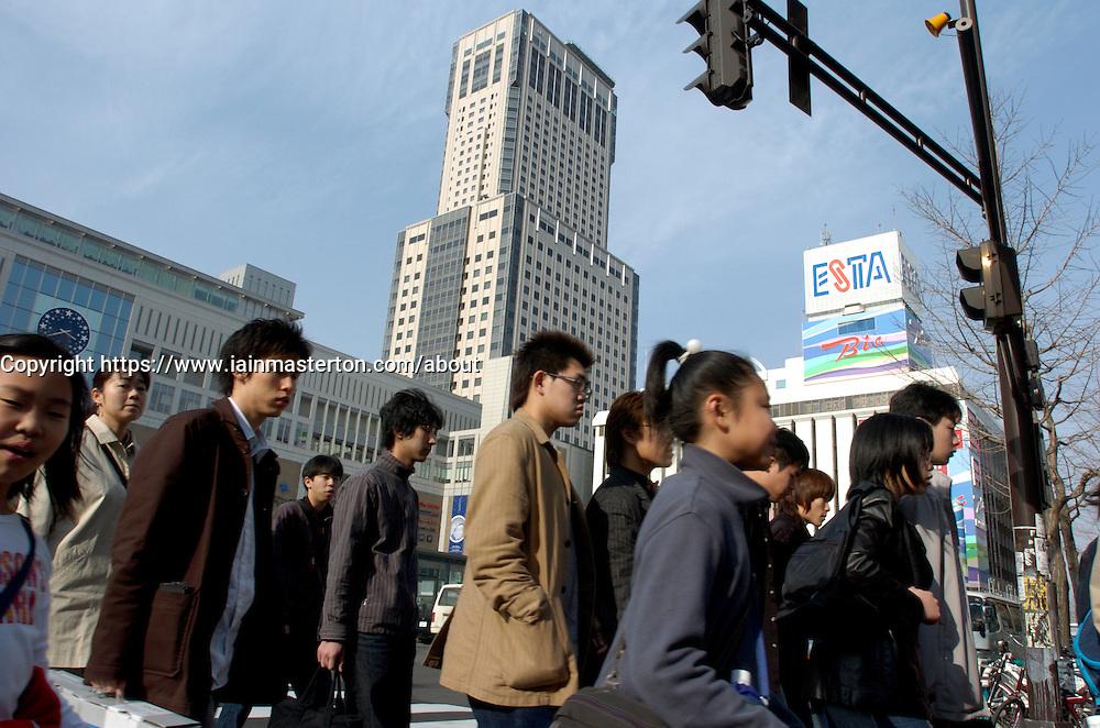 Pedestrians crossing street in front of modern railway station complex in Sapporo Hokkaido Japan